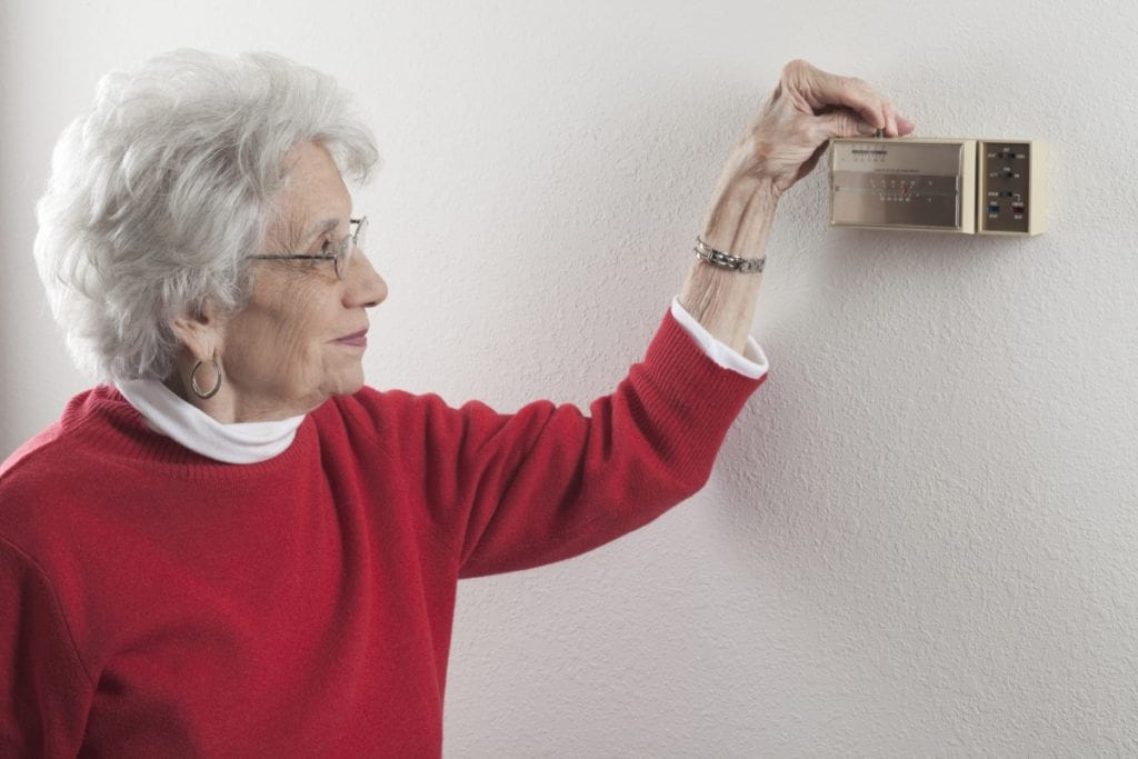 woman adjusting thermostat, thermostat