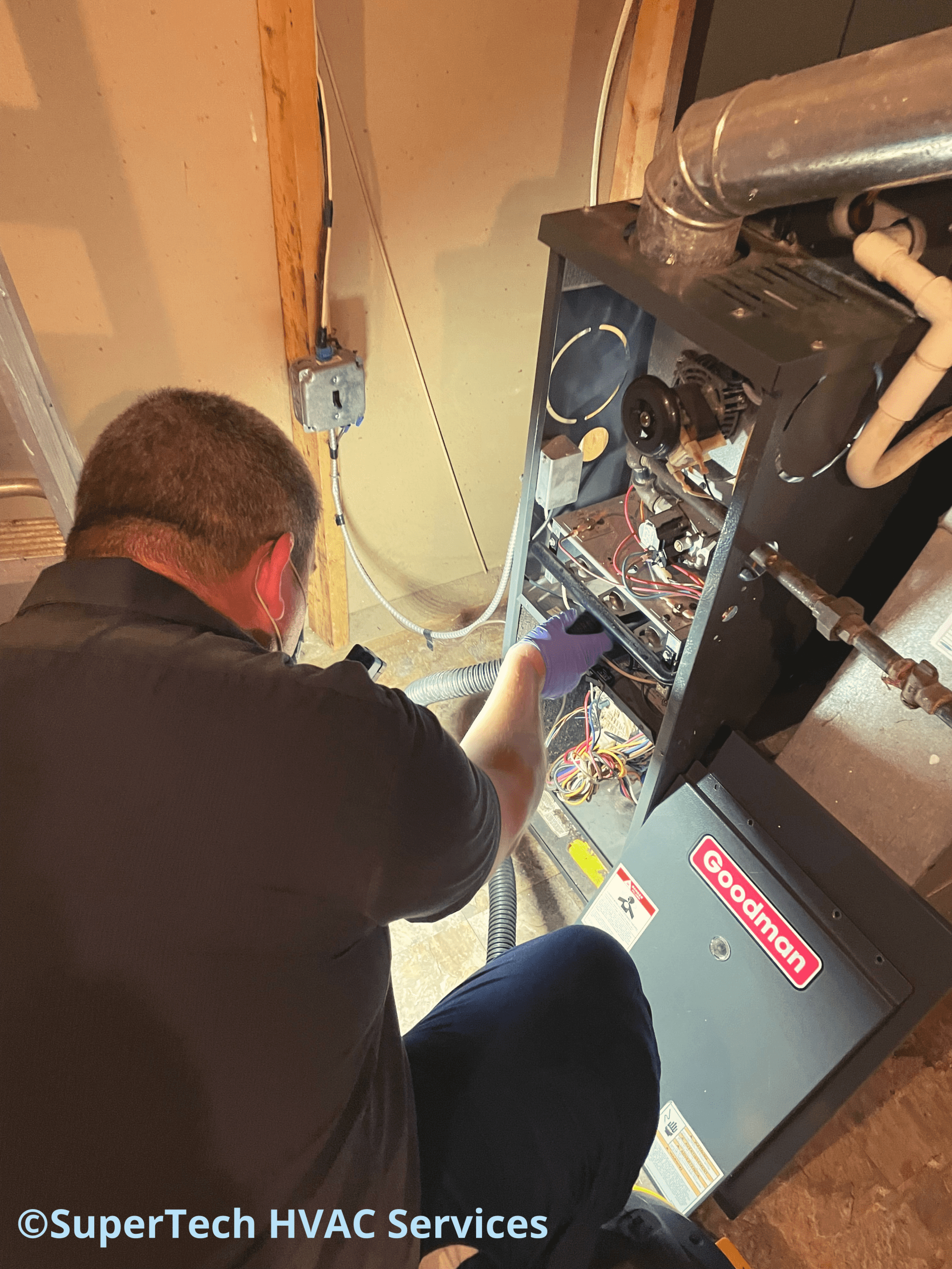 Charlie vacuuming cabinet during furnace tune up